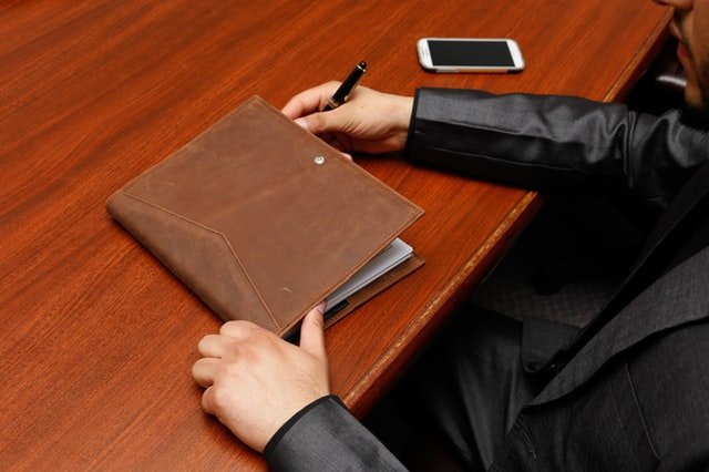 one member of a data governance executive steering committe seated at a desk with a notepad
