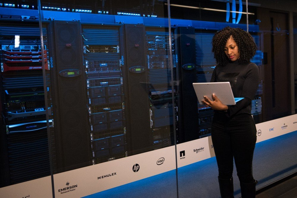 woman standing in front of row of servers implementing data stewardship best practice