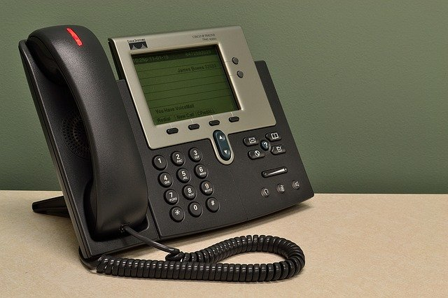 a desktop on a table telephone connected to a call centre analytics system