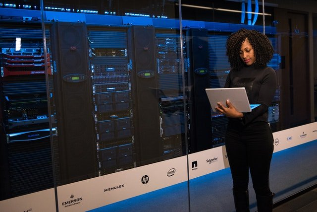 woman standing in front of cloud computing server assessing virtual machine cross border risk
