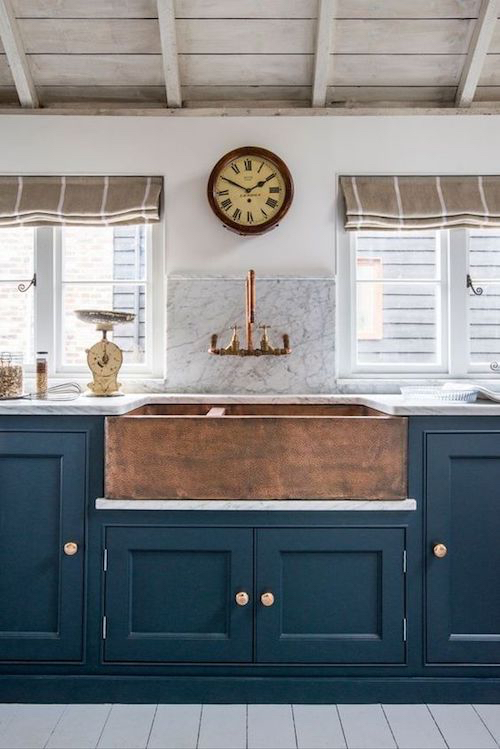 a-copper-farmhouse-kitchen-with-blue-cabinets-and-a-mix-of-different-brass-finishes-from-the-faucet-to-the-cabinet-knobs