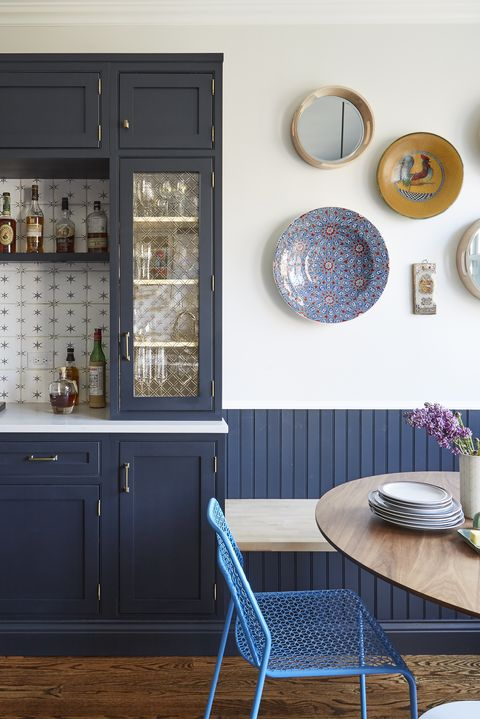 Navy blue kitchen storage hutch with decorative plates on the wall