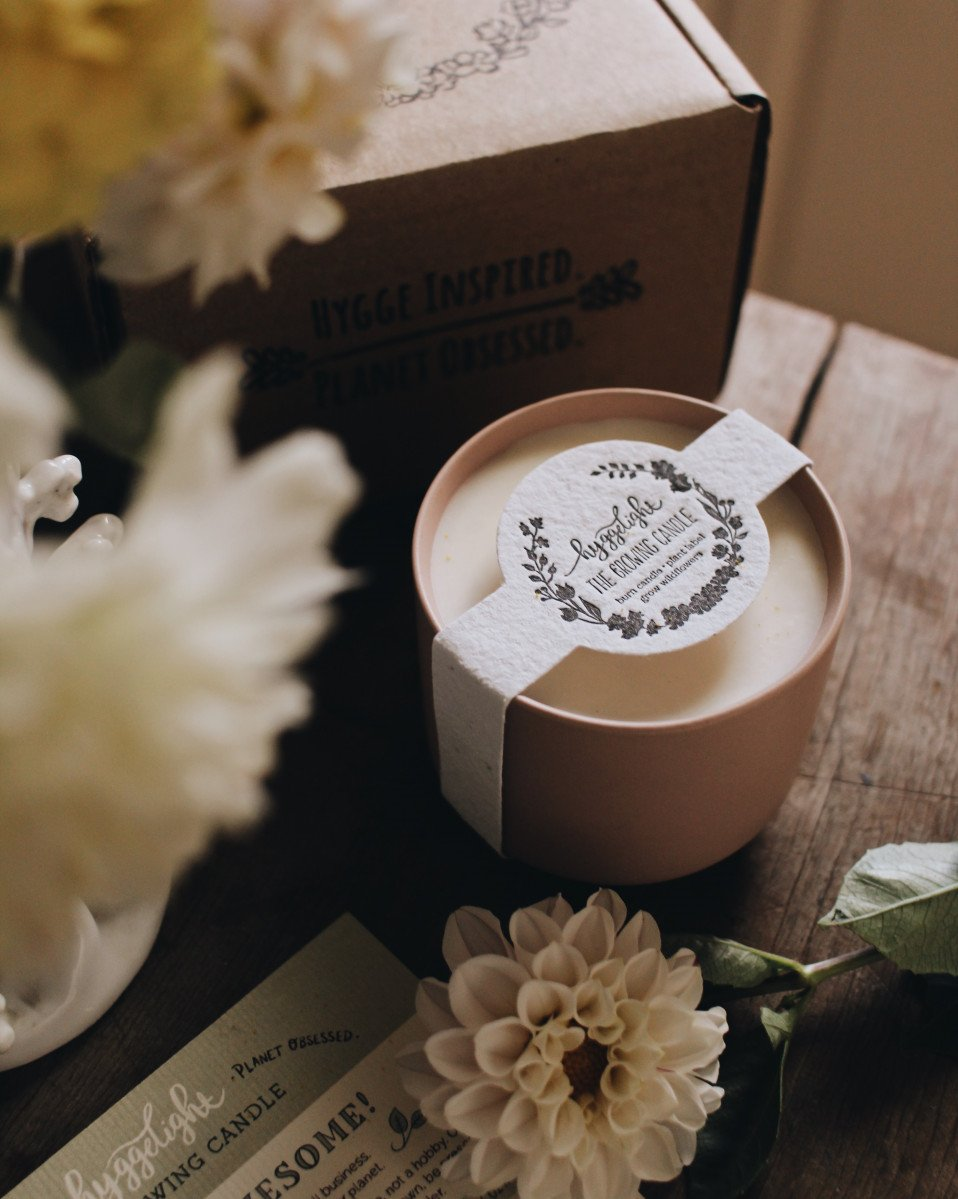 The Adelyn Growing Candle beside flowers and zero-waste packaging from company Hyggelight in Toledo, Ohio.