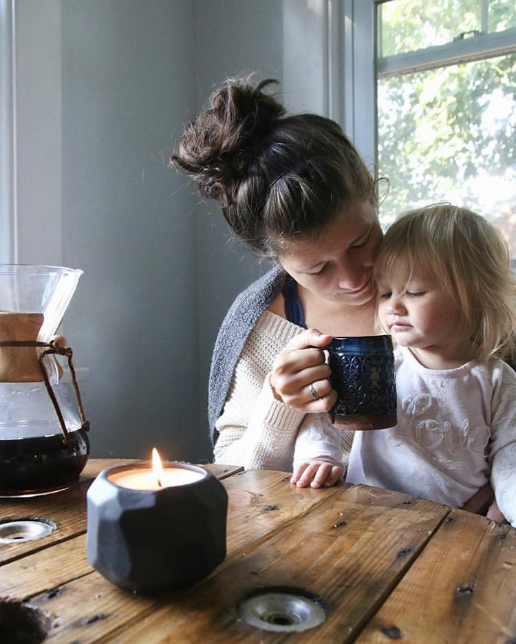 Mom and daughter share morning snuggles next to coffee and growing candle