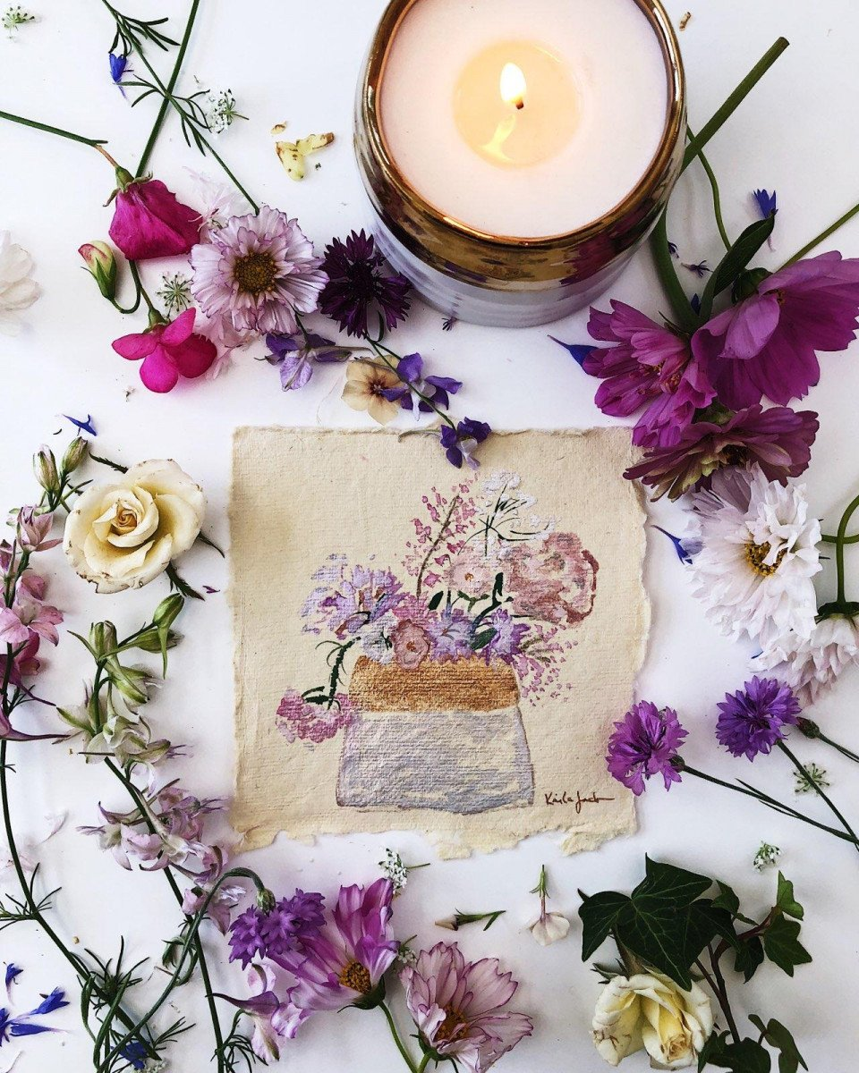 Fragrance of lavender displayed in Clara Growing Candle next to artwork and assorted wildflowers
