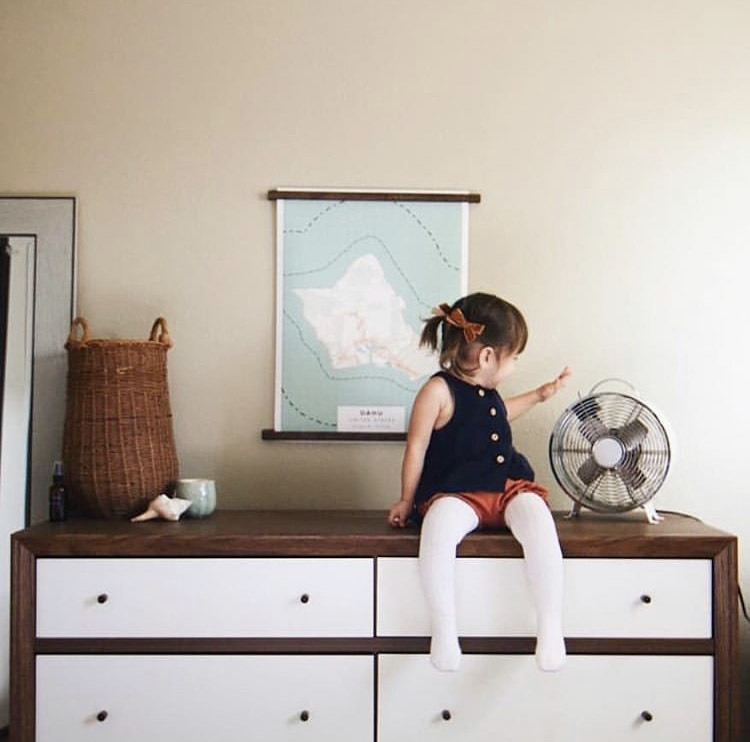 Mom looks on as little girl sits on top of dresser