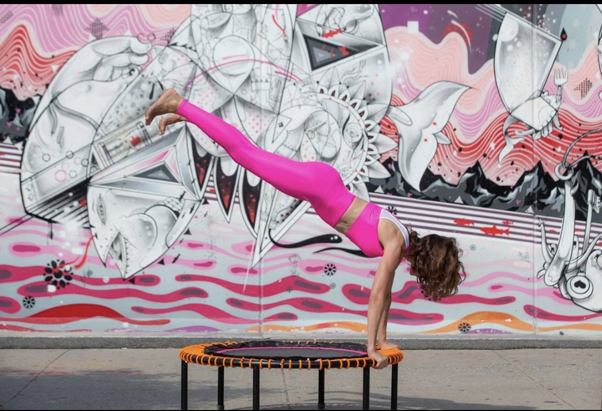woman in pink workout set jumping on a rebounding trampoline