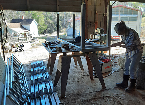 Michele preparing reclaimed carport materials for welding into greenhouse tables.