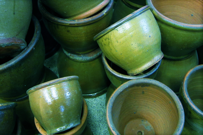 a photo of turquoise ceramic pots with drainage holes