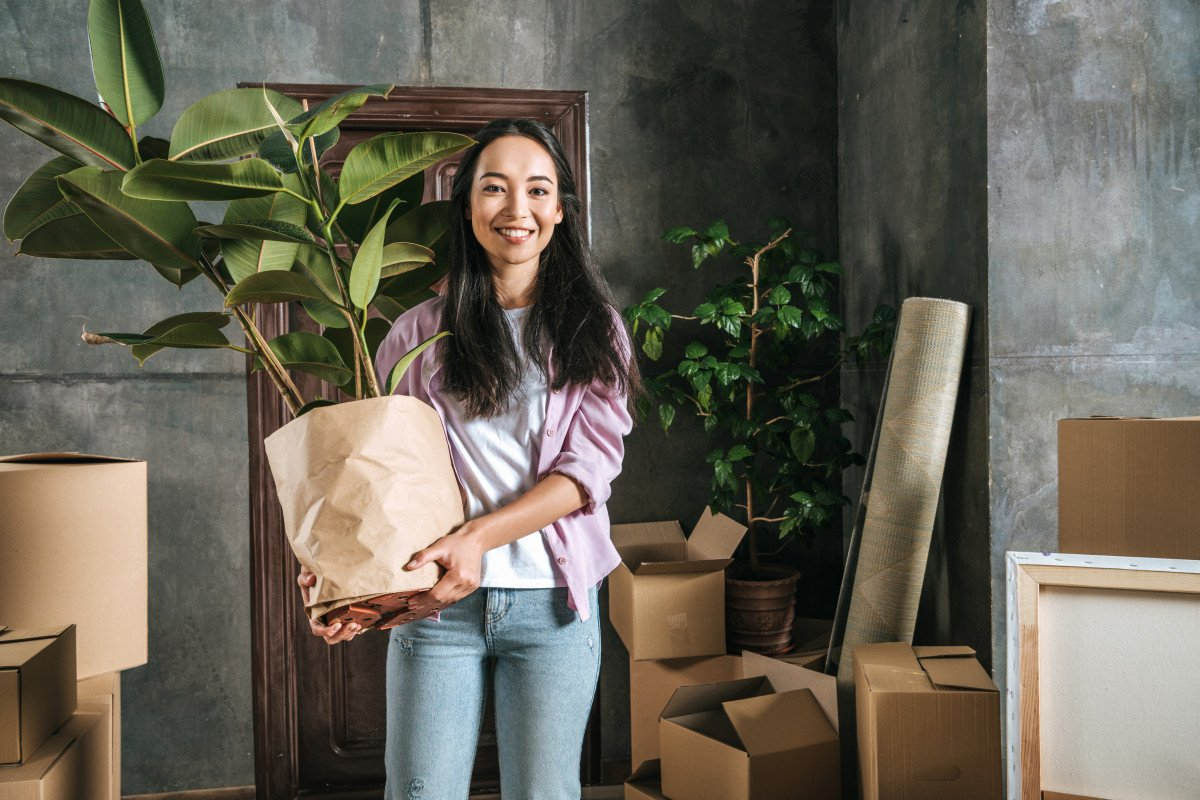 A photo of a person holding a rubber plant. The planter is wrapped with brown paper.