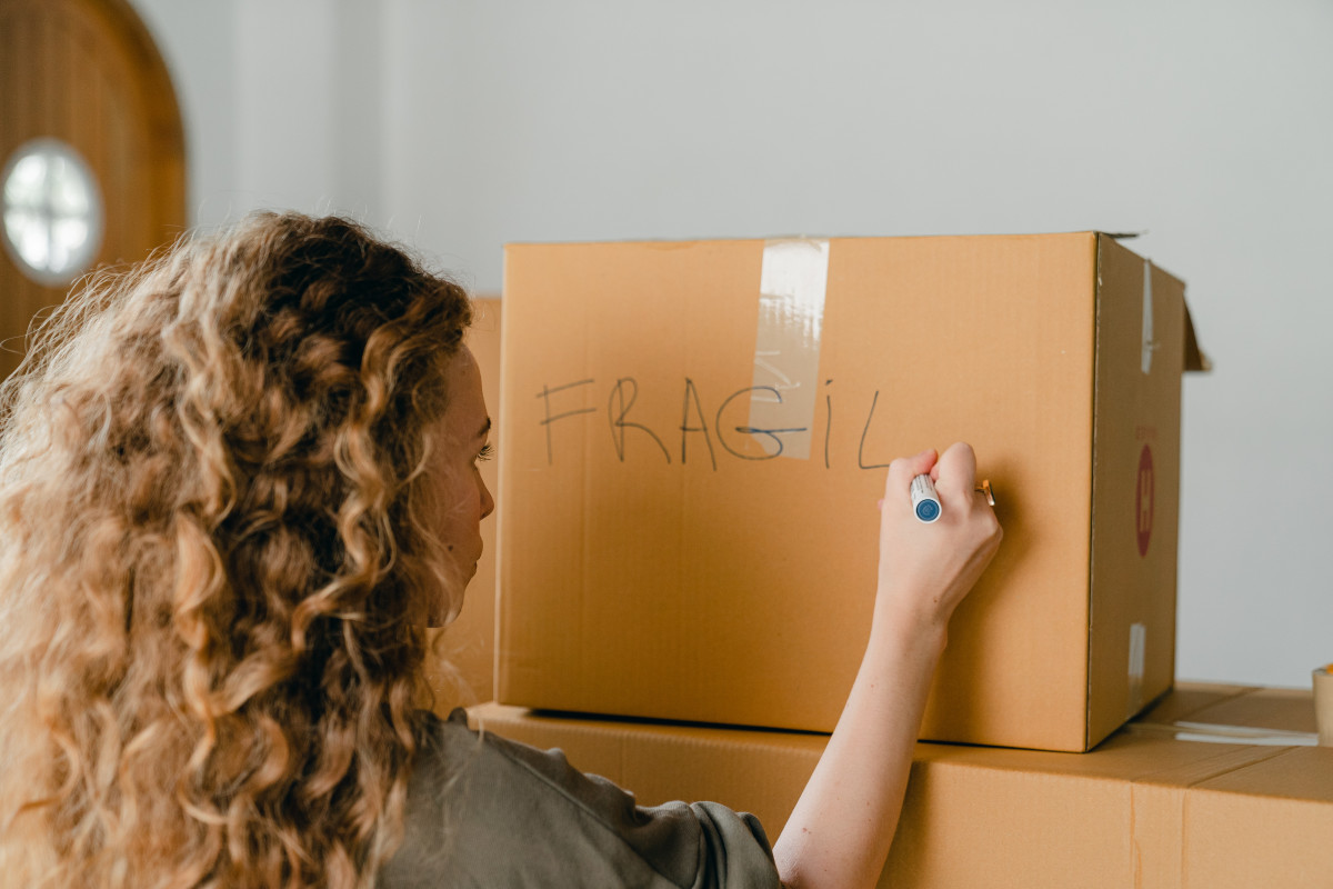 "A photo of a person writing the words ""FRAGILE"" on a closed box"